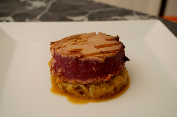 tun marinado sobre cama de cebolla caramelizada